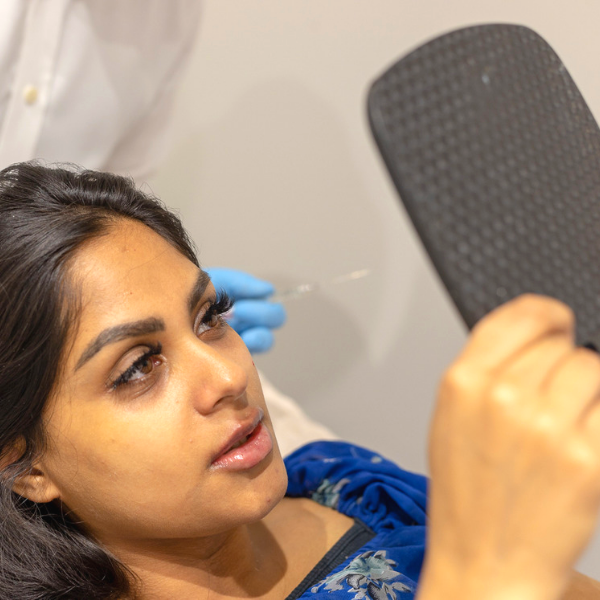 non-surgical nose job in london image of woman lying down on a treatment bed holding up a hand mirror and looking at her face terms and conditions