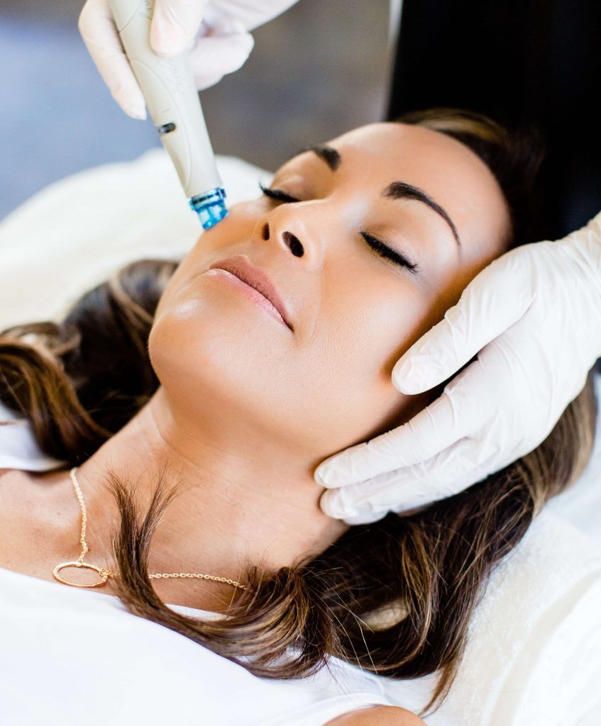 hydrafacial in north london image of woman lying down on a treatment bed getting a hydrafacial treatment